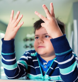 young boy wearing a blue striped shirt counting to seven on his fingers
