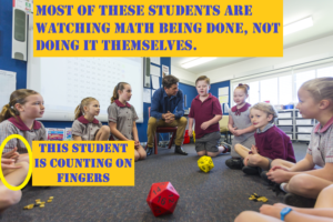 Students and teacher playing multiplication games with dice sitting in a circle in a classroom, to learn math facts.