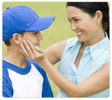 A mom congratulates her son at a baseball game.