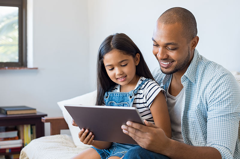 father and daughter logging into rocket math online game using tablet