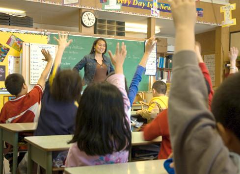 Teacher standing in front of class teaching finding factors.